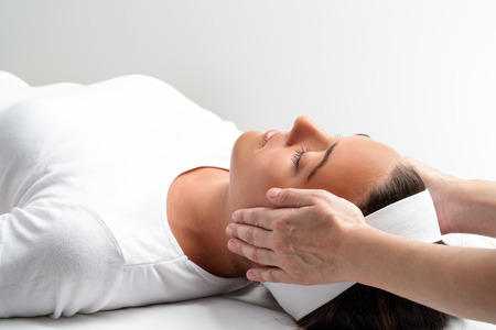 treatments: Close up of practitioner doing reiki with hands on young woman. Therapist doing healing treatment with hands next to head. Stock Photo