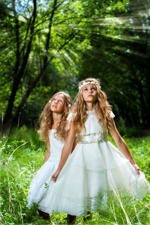 Portrait of two little princesses wearing white dresses in forest.