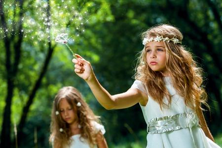 Fantasía retrato de niña linda con la varita mágica en el bosque.