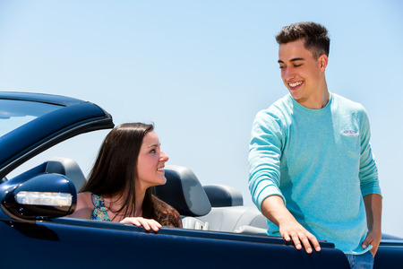 door man: Portrait of young man opening car door to woman. Young girl sitting in blue convertible.