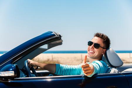 Portret atrakcyjne młody człowiek siedzi w niebieskim wymienialnych robi kciuk do góry.