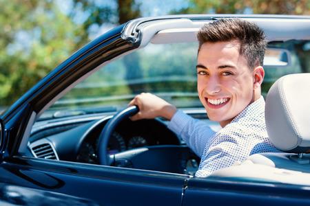 Portrait d'adolescent attrayant assis dans la voiture. Jeune homme assis dans convertible dans le siège du conducteur. Banque d'images