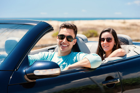 drive car: Close up portrait of handsome young man driving convertible along seaside with girlfriend sitting in back.