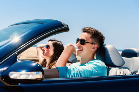 Portrait of attractive young man driving with girlfriend in blue cabriolet.