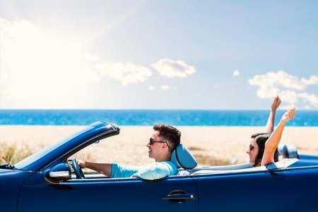Close up portrait of young man driving blue convertible. Girlfriend sitting in back raising arms in air.