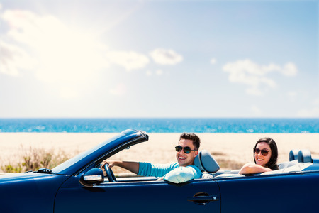 Close up portrait of cute teen couple driving blue cabriolet along seaside.