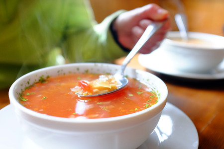 hot soup: Macro close up of hand holding spoon with hot bowl of soup. Spoon with hot steamy bowl of vegetable soup.