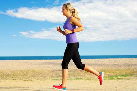 Close-up beweging portret van aantrekkelijke jonge vrouw joggen langs het strand in de late namiddag.