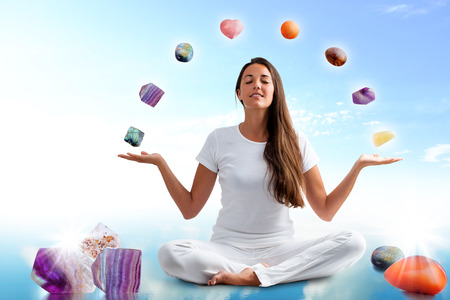 spirituality therapy: Full length portrait of young woman dressed in white doing yoga with precious gemstones.Conceptual dream scape with colorful gemstones floating around girl. Stock Photo