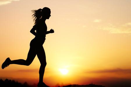 pista de atletismo: Cierre de la silueta de la acci�n de corredora en sunset.Girl con retroiluminaci�n contra el cielo de color naranja intenso.