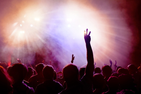 light beams: Dancing Crowd of young people dancing at disco. People Raising hands against purple and pink smoky background with light beams. Stock Photo