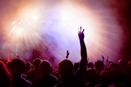 bewegung menschen: Tanzen Menge von jungen Menschen in Disco tanzen. Menschen Anhebung H�nde gegen lila und rosa rauchigen Hintergrund mit Lichtstrahlen. Lizenzfreie Bilder