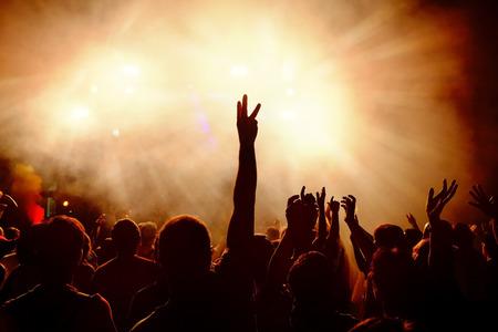 Silhouetten van feestelijke menigte van jonge mensen dansen op muziek festival. Verhoging handen tegen rokerige oranje achtergrond met lichtstralen. Stockfoto