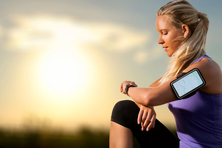 watch: Portrait of young athlete checking workout on smart watch at sunset.Woman wearing armband with smart watch and graphic showing workout results. Stock Photo