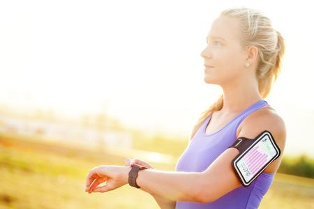 피트니스 차트 스마트 시계에 보여주는 스포츠 착용 스마트 watch.Girl에 매력적인 젊은 여자 설정 운동의 초상화를 닫습니다.