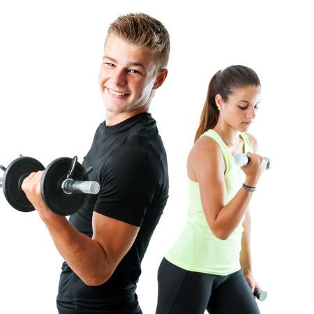 Close up retrato de muchacho adolescente hermoso que se resuelve con weights.Out de la chica enfoque de trabajo en background.Isolated en blanco.