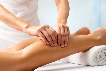 massage: Detail of hands massaging human calf muscle.Therapist applying pressure on female leg.