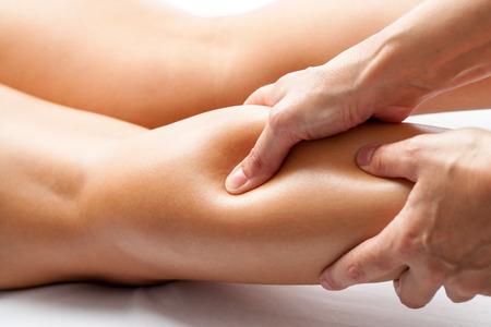 massieren: Extreme Nahaufnahme von Osteopathen Anwendung von Druck mit dem Daumen auf die weibliche Wadenmuskel. Lizenzfreie Bilder