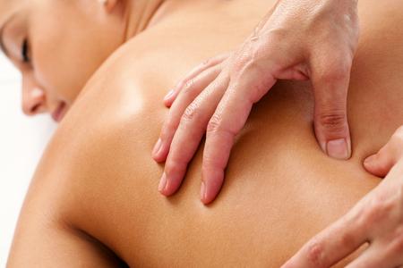 Macro close-up van de handen doen manipulatieve massage op vrouwelijke rug. Stockfoto