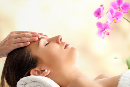 massages: Close-up portrait de jeune Massage du visage Femme dans le spa. Thérapeute de massage de la tête de la femme contre un fond lumineux et coloré.