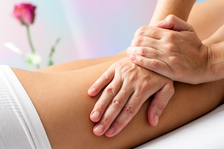 Close up Detail of Hands massaging female hamstrings. Therapist doing manipulative treatment on upper back leg.