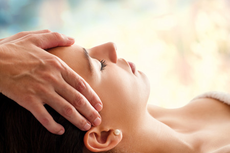 Close up head portrait of young woman having facial massage in spa. Therapist massaging woman's head against colorful background. Stock Photo