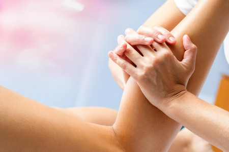 Macro close up of osteopath massaging female calf muscle. Hands manipulating lower leg muscle. Stock Photo