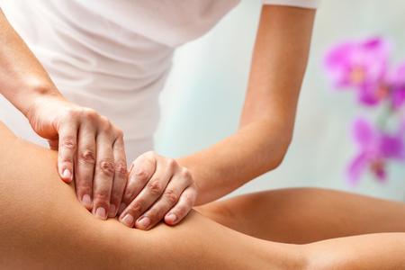 muslos: Terapeuta que hace el masaje de rehabilitación con las manos en los isquiotibiales de sexo femenino. Foto de archivo