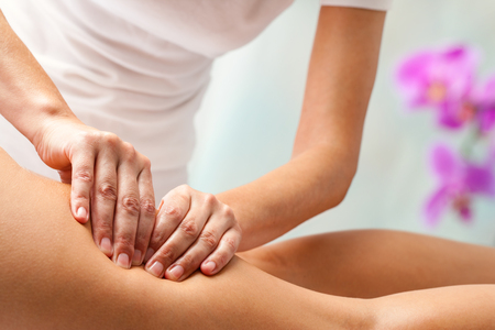 massage: Therapist doing rehabilitation massage with hands on female hamstrings. Stock Photo