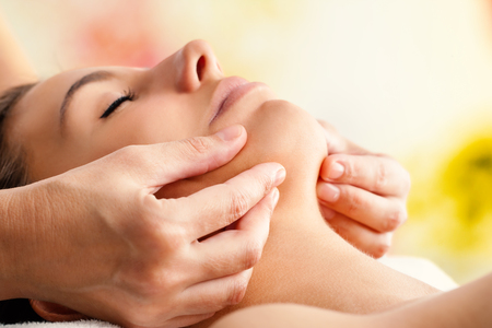 head in hands: Macro close up of Hands massaging female chin. Therapist applying pressure with fingers on face. Stock Photo