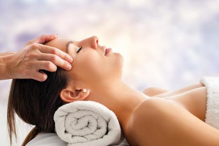 Close-up portret van aantrekkelijke jonge vrouw die ontspannen gezichtsmassage. Therapeut masseren vrouw hoofd tegen heldere kleurrijke achtergrond.
