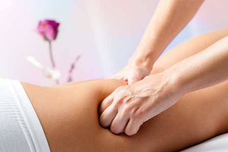 manipulation: Close up of therapist hands massaging female hamstrings on leg.