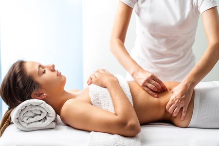 Close-up van osteopaat doen manipulatieve massage op vrouwelijke buik. Stockfoto
