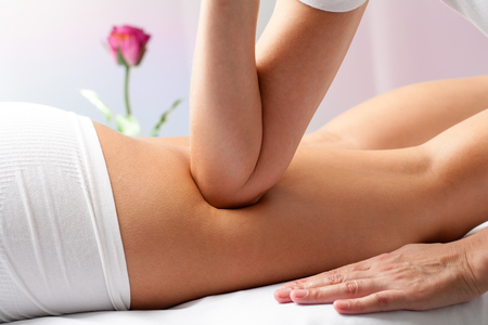 osteopath: Close up of therapist applying pressure on female hamstrings with elbow.