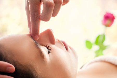 extreme macro: Macro close up of  relaxing facial massage. Therapist applying pressure with fingers between eyes.