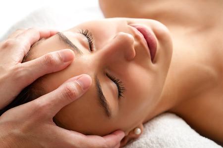 masaje: Cierre de tiro de cabeza de la mujer que tiene masaje facial curativo. Terapeuta aplicar presión con los pulgares en la frente. Foto de archivo