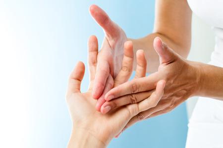 manos juntas: Macro cerca de las manos del terapeuta haciendo masaje curativo en la mano femenina. Foto de archivo