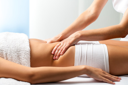 healing practitioners: Close up of osteopath doing manipulative abdomen massage on female patient. Stock Photo