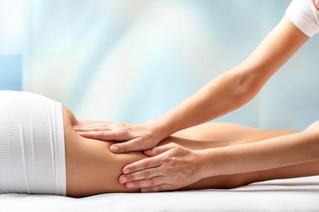 hamstrings: Therapist massaging upper back part of female leg. Hands applying pressure on hamstrings.