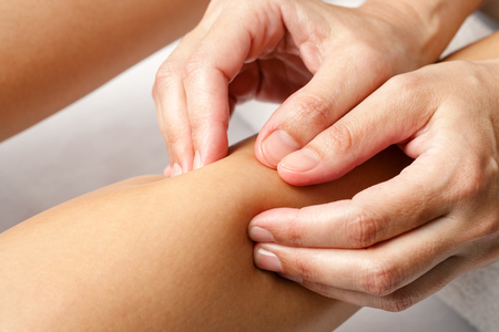 lower body: Macro close up of hands doing rehabilitation massage on female calf muscle.