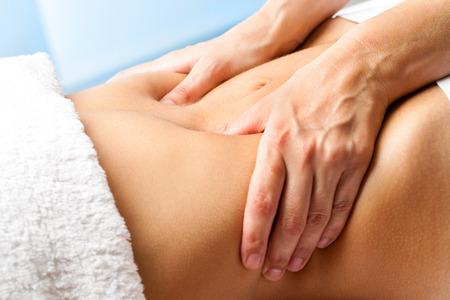 Macro close-up van de handen masseren vrouwelijk abdomen.Therapist druk uit te oefenen op de buik.