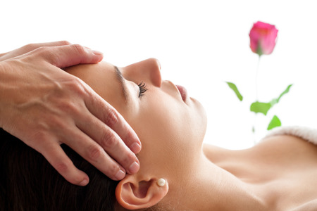 massage: Close up portrait of Woman having Facial massage. Therapist massaging woman's head isolated against white background. Stock Photo