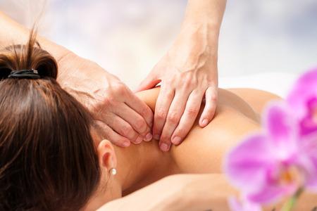 Macro close-up van de handen masseren vrouwelijk nek en schouders. Stockfoto