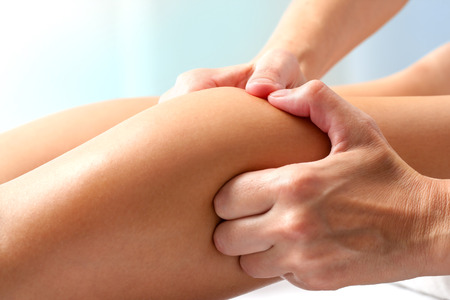 body care: Macro close up of hands doing manipulative healing massage on female calf muscle.