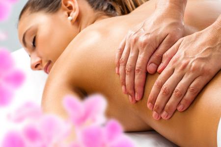 Primer plano de las manos haciendo relajante masaje de espalda de mujer en spa.