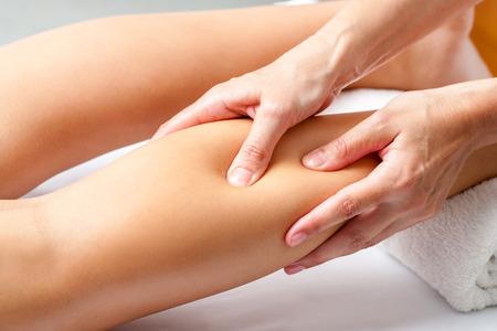 Macro close-up van de handen druk uit te oefenen met de vingers op de kuitspier. Osteopaat doen helende massage op vrouwelijke been. Stockfoto