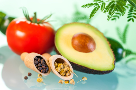 green herbs: Macro close up Still life of Naturopathic products.Avocado with herbs and seeds against green background.