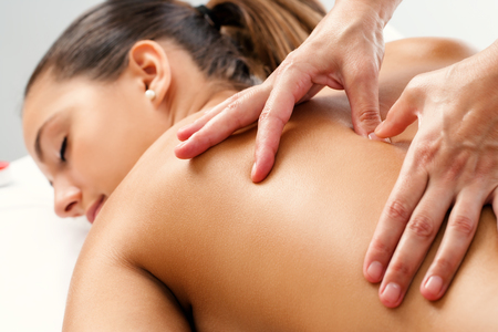 hands massage: Close up of Therapist doing curative healing massage with thumbs on female back. Stock Photo