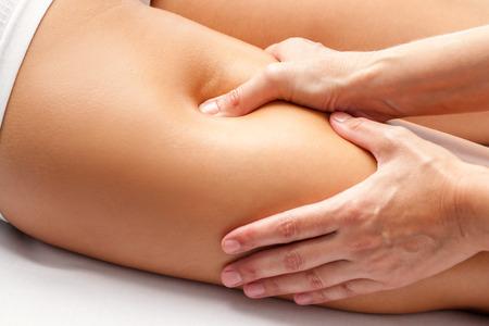 legs: Macro cerca de las manos del fisioterapeuta masajear los m�sculos isquiotibiales de la mujer atleta. Foto de archivo