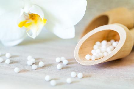 homeopatia: Macro cerca de las bolas homeopáticos con la orquídea.